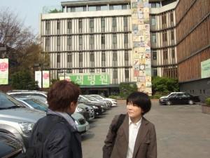 緑病院を背景に満田さんとキムさん